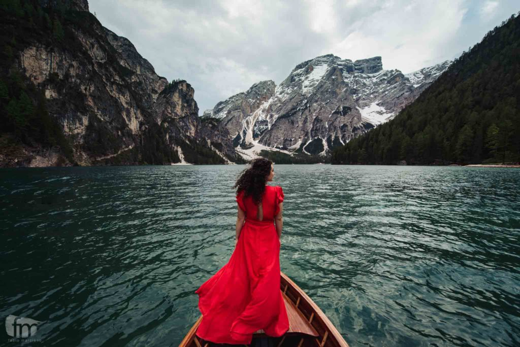 bride with red dress on Lake Braies on the Dolomites