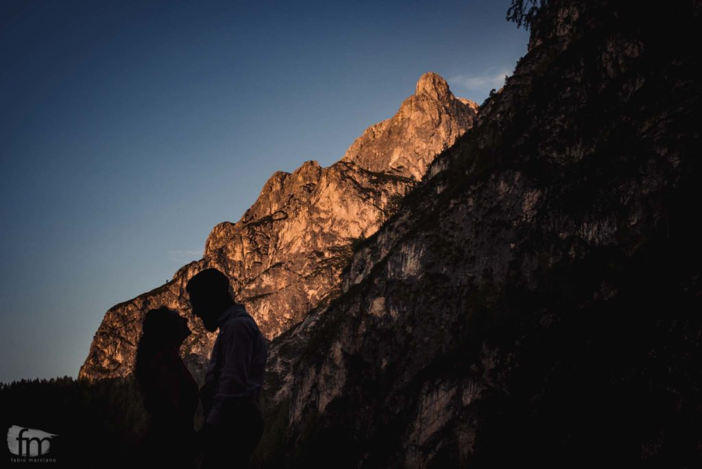 silhouette of a couple on a rocky wall of Lake Braies