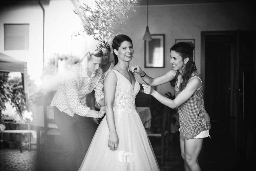 Sposa viene aiutata dai testimoni durante la vestizione