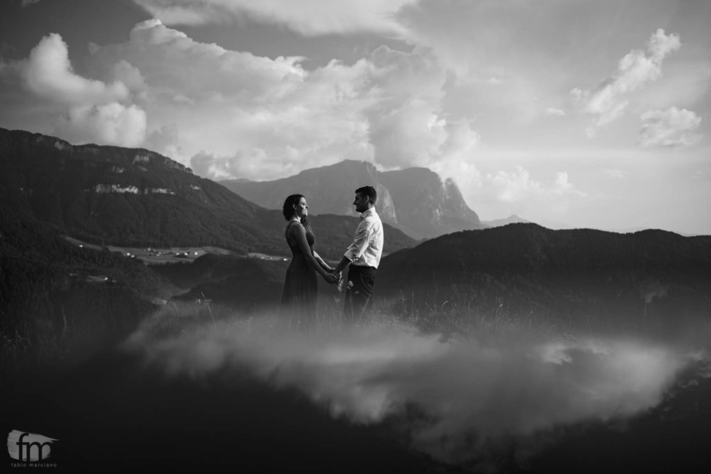 Couple of future bride and groom facing each other on the dolomites
