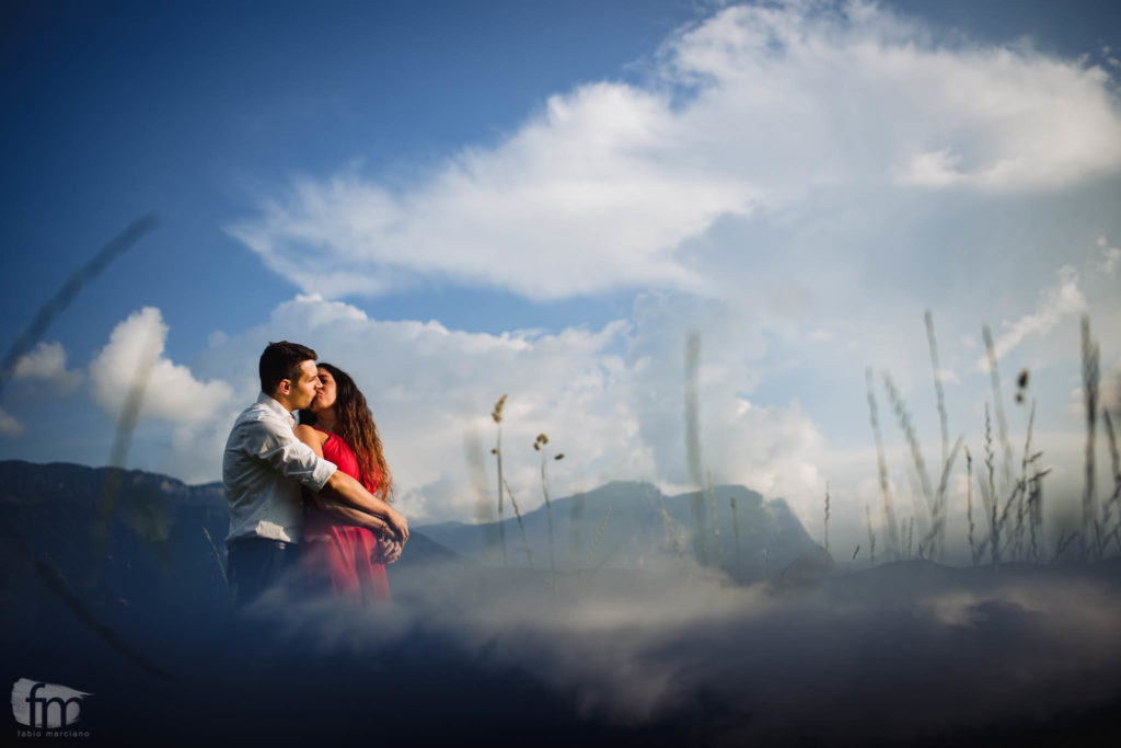 Groom and bride kissing each other with the blue sky background.