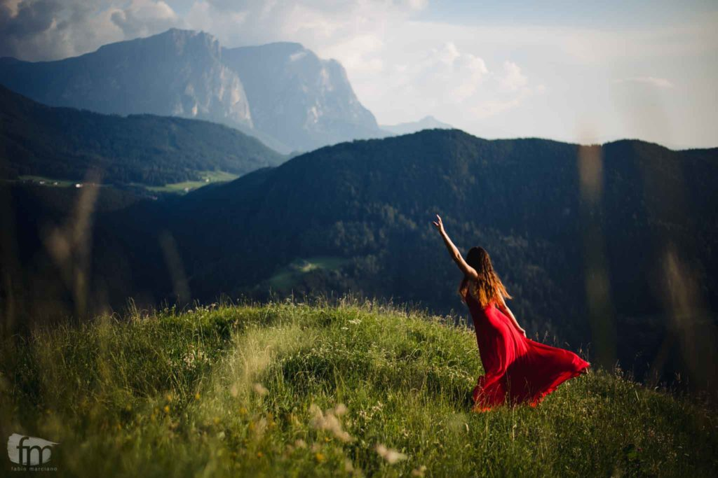Bride with red dress dancing in the panorama of the Seiser Alm.