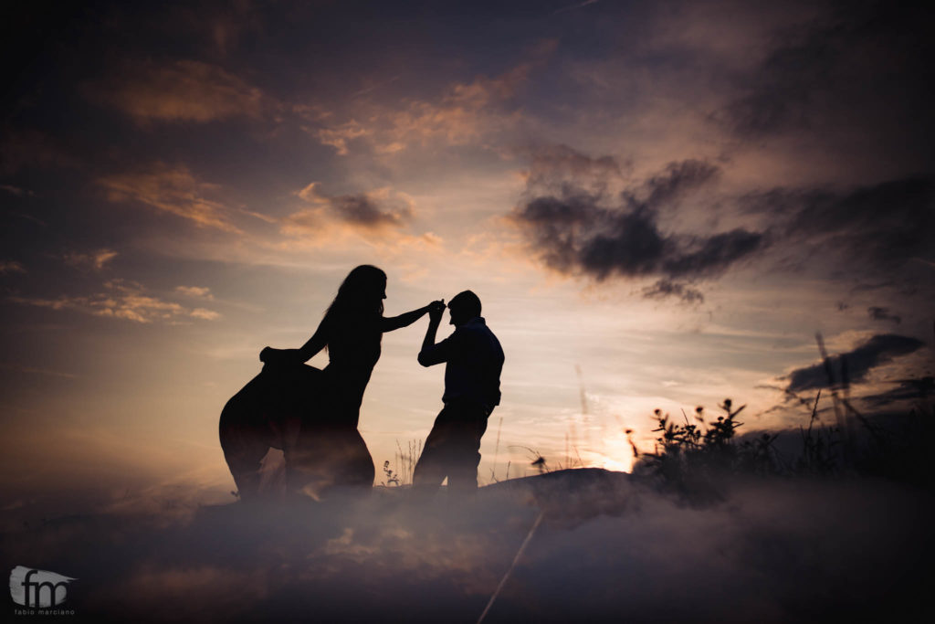Silhouette of bride and groom dancing at sunset in the Dolomites.