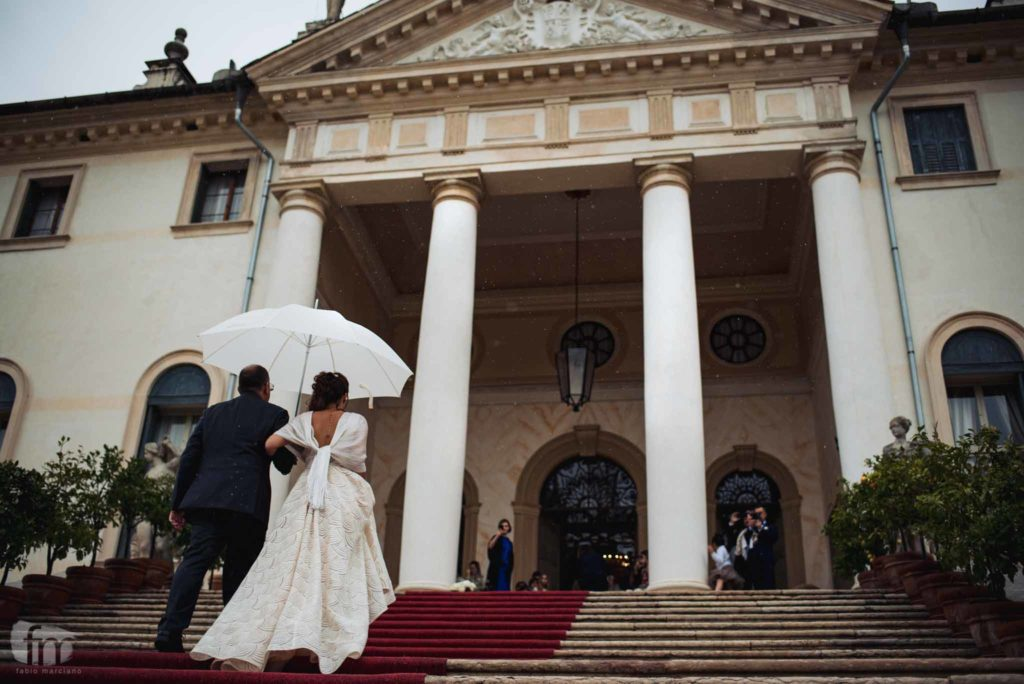 bride climbs the steps of the villa corner of the queen with her father
