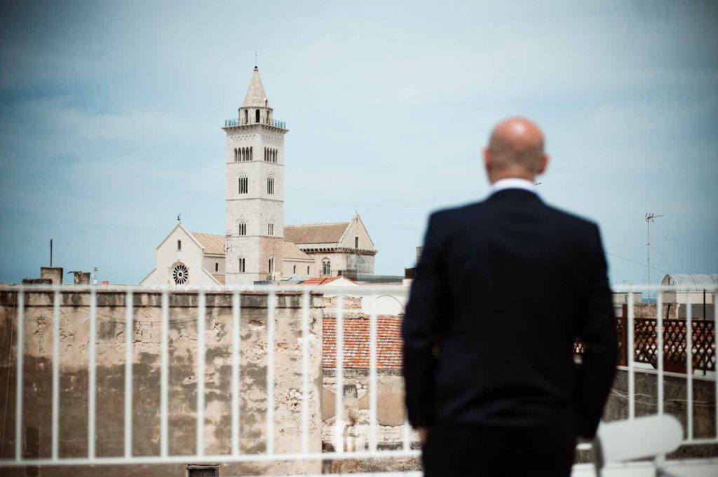 Groom getting ready with view of the cathedral of Trani