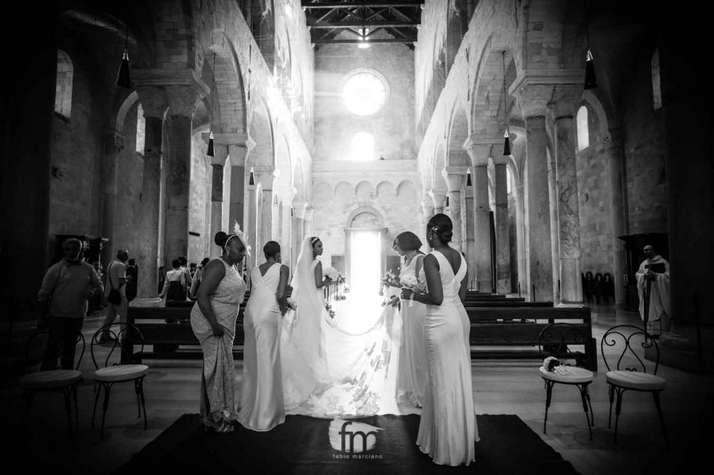 the bridesmaids hold the veil of the bride in the Cathedral of Trani